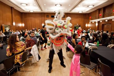 A young girl feeds a donation card to a man dressed in a traditional Vietnamese dragon costume at the IMU Main Ball Room in Iowa City.