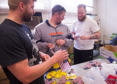 student veterans prepare flags for a Veteran's Day flag display