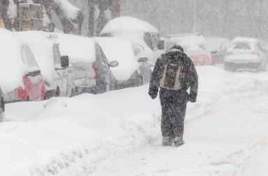 Winter weather photo of student truding along a street during a blizzard