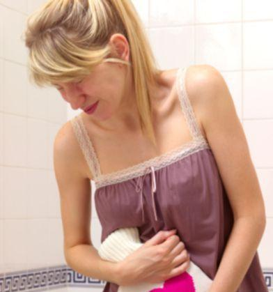 A woman with endometriosis clutches a heating bag with a pink heart on it to her stomache to alleviate the pain