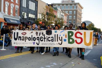Students with #blacklivesmatter banner walk in homecoming parade.