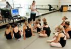 A dance instructor talks to a group of students gathered around a video monitor.