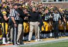 Raymond Daniel, right and line judge Mike Sharp flank Iowa coach Kirk Ferentz during Saturday's game.