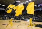 Male cheerleaders run the Iowa Tigerhawk and I flags onto Carver Hawkeye Arena's court.