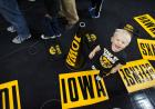 A young boy stands on an IOWA cheer card.