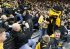 Woman posing with Iowa's mascot Herky in the crowd.