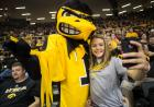 Herky poses with a young woman who snaps a picture on her phone.