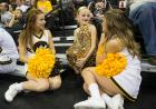 Cheerleaders talk to a little girl in a gold sequined outfit.