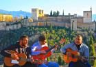 """High up in the mountains with a view of the enchanted Alhambra and snowcapped mountains, a trio of Spanish men sit and play traditional Spanish music with their guitars as people stare out into the endless beauty of Granada."" This photo, ""Musica en l"