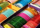 Colorful Indian bracelets line a table.
