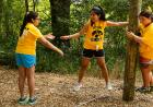Three students hold hands while working through an obstacle course as part of a team building activity in The Iowa Edge Program.