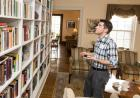 A young man looks at a tall bookshelf.