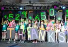 Children hold up signs with the number 1,529,650.19 and the letters T H A N K S on a stage.