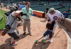 A photographer takes a photo of a man in a Cubs jersey playing with his 9 year-old daughter on a baseball field.