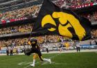 Iowa mascot Herky runs onto a football field flying a Tigerhawk flag.