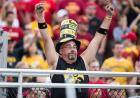 A man in Iowa Hawkeye gear raises his fists in the air in celebration.