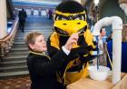 A young child looks at a display with Herky.