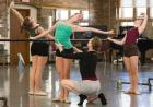 Three female dancers at the ballet barre, one dance instructor holding her fingers on the nearest dancer's stomach and back.