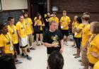 A man in a black t-shirt surrounded by people in yellow t-shirts in a classroom.