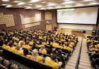 A lecture hall full of students in yellow t-shirts.