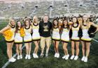 A man in a black t-shirt posing with a group of women cheerleaders.