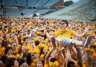 Man held aloft by a yellow-shirted crowd.
