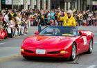 A woman in a yellow jacket riding on a red corvette in a parade.