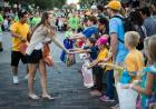 A girl gives candy to young children on a parade route.