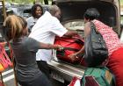Family members pull a large suitcase from a car trunk.