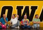 "Fans sit in front of the ""IOWA"" sign"