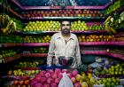 A man stands in the middle of a fruit stand in a market in Mumbai, India