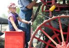 A young girl helps drive a big steam tractor.