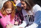 A student signs her name to the cooler which will be lfited by the balloon.