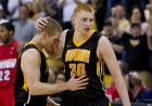Iowa basketball player Matt Gatens (5) leans his head agains the right arm of Iowa basketball player Aaron White (30) with his eyes closed in the final seconds of the game.