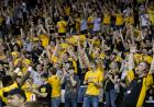 A crowd of Hawkeye fans cheers and throws their arms in the air for an Iowa basket (not pictured).
