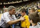 Iowa head football coach Kirk Ferentz autographs the yellow t-shirt of a young Iowa fan at courtside in Carver-Hawkeye Arena.