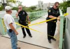 Police stretch caution tape across the entrance to the IMU footbridge.