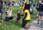 Herky kneeling down, interacting with child