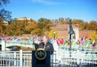 flags representing the home countries of university of iowa international students fly on the IMU footbridge; president bruce harreld speaking at ceremony