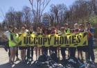"""A group of students hold an """"Occupy Homes"""" sign during a service learning project."""