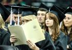 graduate reads during commencement ceremony