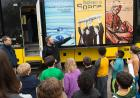 Museum educator talks with elementary school students in front of the Mobile Museum.