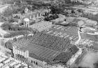 Live action on the gridiron is caught in this photo from the early 1960s. Adjacent to Iowa Stadium (it wouldn't be known as Kinnick Stadium for a few more years) are temporary student housing barracks. Also visible in the image: Boyd Tower and General Hos