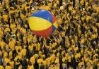 Students in gold shirts bouncing a beach ball