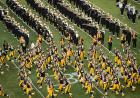 The football team takes the field as the band looks on.