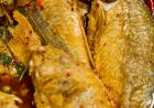 Cooked fish with their heads and scales intact lie in a serving dish with sauce and spices.