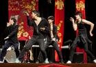 Four men wearing black pose mid-dance on stage with red Vietnamese draperies behind them.