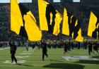 IOWA flags lead the team out of the tunnel