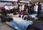 Team members and sponsors with the car in the garage.