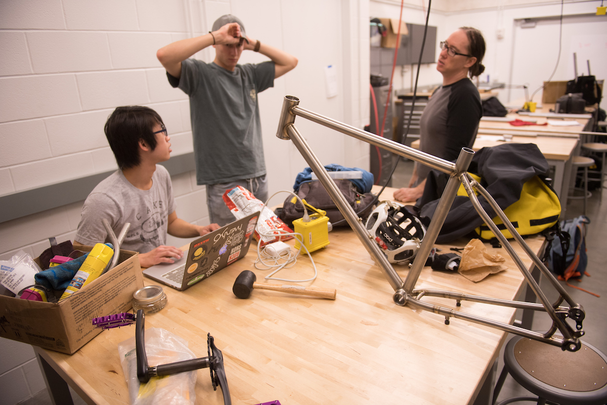bike-building students talk around table that has bike frame atop it